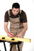 Man measuring plank of wood — Stock Photo