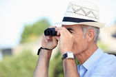 Old man looking through binoculars — Stock Photo