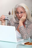 Old woman with credit card and computer — Stock Photo