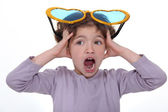 Little girl screaming with huge funny sunglasses on head — Foto Stock