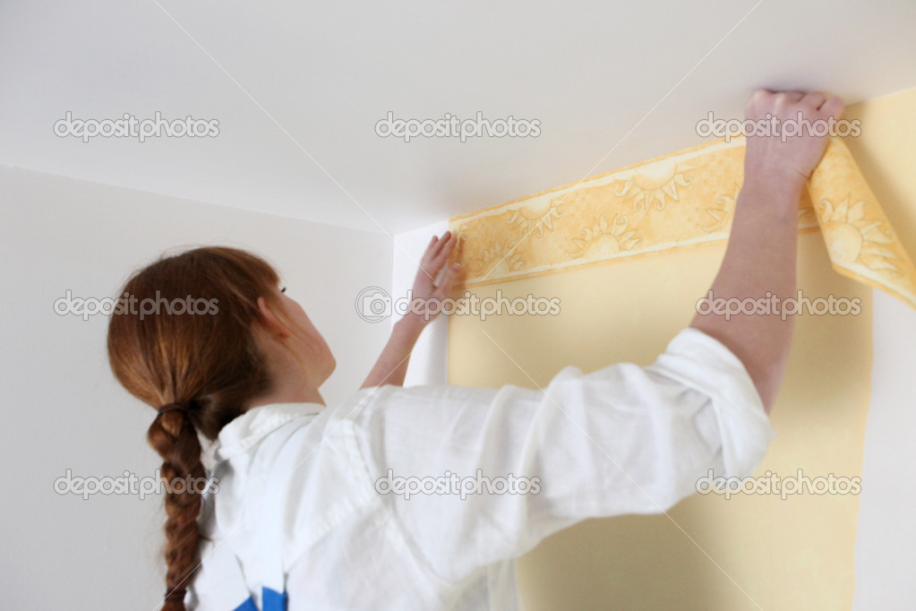 Woman putting up wallpaper — Stock fotografie #10839204