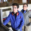 Young intern operating factory saw — Stockfoto