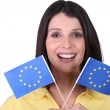 Brunette  brandishing European flags - Stock Photo