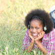 Stock Photo: Girl lying on grass with headphones
