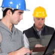 Young craftsman working on his laptop while senior craftsman is taking notes — Stock Photo #10842917