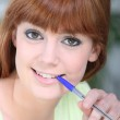 Young woman chewing on a pen — Stock Photo