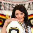 Female German soccer supporter stood holding ball — Stock Photo #10843441