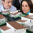 Architect showing scale model of house to buyers — Stock Photo