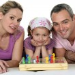 Parents and little girl playing chess together — Stock Photo