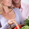 Couple laughing with vegetable basket. — Stock Photo #10844868