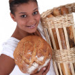 Female baker holding bread, studio shot — Stock Photo
