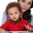 Portrait of young mother with mixed-race child drawing with wax sticks — Stock Photo