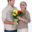 Son giving mother flowers - Foto de Stock