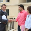 Stock Photo: Couple shaking hand of real estate agent