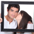 Stock Photo: Young couple kissing in frame
