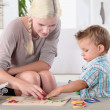 Mother and child completing jig-saw — Stock Photo