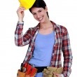 Tradeswoman putting on her hard hat — Stock Photo
