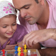 Father and daughter playing board game — Stock Photo