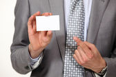A cropped picture of a businessman showing his card. — Stock Photo