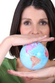 Woman holding miniature globe — Stock Photo