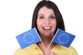 Brunette brandishing European flags — Stock Photo