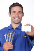 A 35 years old mechanician is showing a business card — Stock Photo