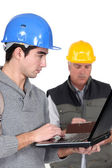 Young craftsman working on his laptop while senior craftsman is taking notes — Stock Photo
