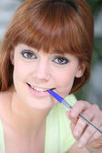 Young woman chewing on a pen — Fotografia Stock