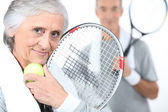 Elderly couple playing tennis — Stock Photo