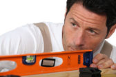Man with spirit level — Stock Photo