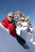 Homme assis par l'homme de neige — Photo