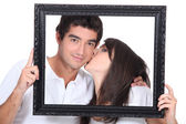 Young couple kissing in a frame — Stock Photo