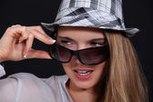 Woman with glasses taking off her hat — Stock Photo