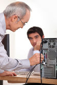 Man plugging a cable into the back of a hard drive — Stock Photo
