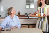 Elderly lady being brought breakfast — Stock Photo