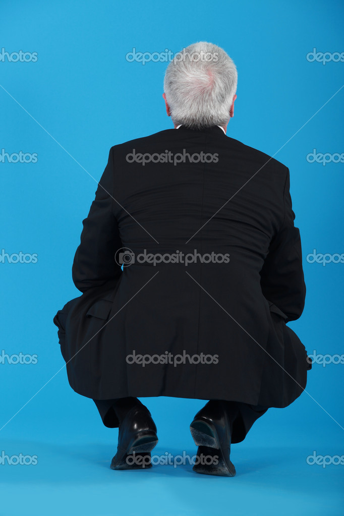 Senior businessman crouching with his back to the camera — Stock Photo #10845527