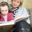 Grandmother reading a story to her granddaughter — Stock Photo