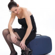 Woman sitting on a suitcase rubbing her ankle — Stock Photo #10851813