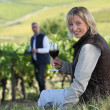 Couple with a glass of wine in the vineyard — Stock Photo