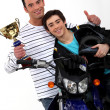 Motorcycle racers holding their trophy - Stock Photo