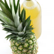 Pineapple next to pineapple juice — Stock Photo