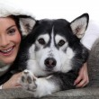 Stock Photo: Womwith her dog on sofa