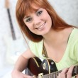 Red-haired woman with electric guitar — 图库照片