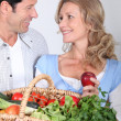 Couple looking into each other's eyes with vegetable basket. — Stock Photo #10854322