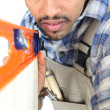 Tradesman using a bubble level - Stock Photo