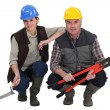Two kneeled construction workers. — Stock Photo