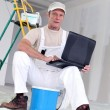 Painter with laptop sat with ladder — Lizenzfreies Foto