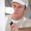 Closeup picture of mature painter holding roller — Stock Photo #10854694