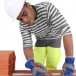 Foto Stock: Bricklayer using ruler