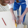 Woman cutting length of wallpaper — Stock Photo
